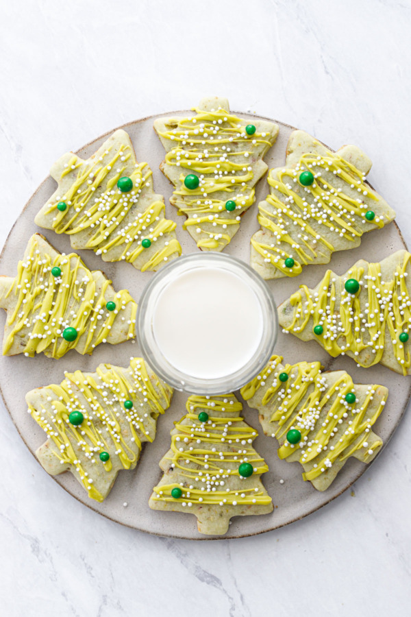 Top down view of tree shaped pistachio sugar cookies arranged in a burst shape around a glass of milk