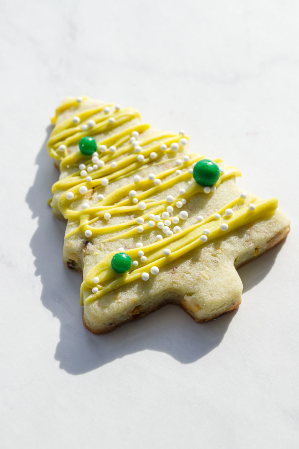 Closeup of a Christmas tree pistachio cookie with a harsh shadow.