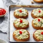Cheesy Artichoke Crostini toasts arranged on a silver baking sheet with a bowl of artichoke topping and pepper drops on the side.