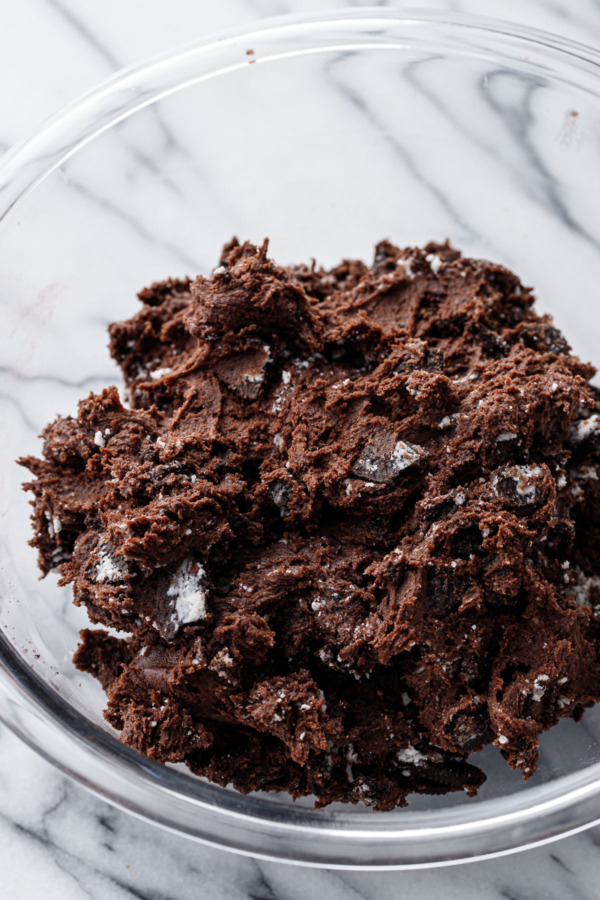 Glass bowl filled with raw chocolate cookie dough mixed with crushed up Oreo chocolate sandwich cookies