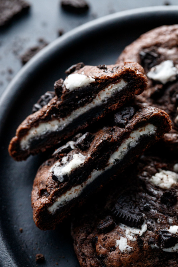 Closeup of a Chocolate Cookies 'n Cream Cookie cut in half to show the cream filling stuffed inside.