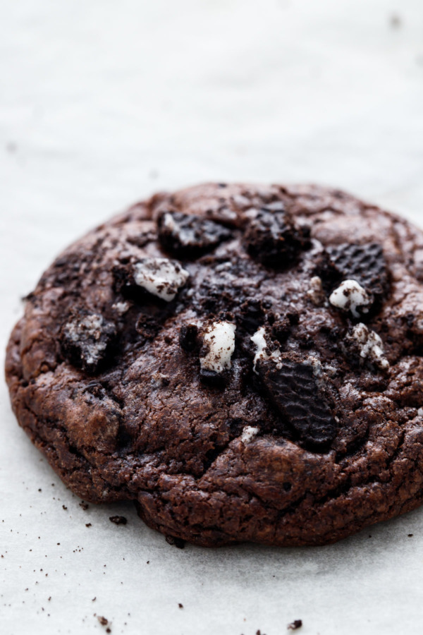 Extreme close up of a baked chocolate cookies 'n cream cookie, topped with pieces of crushed up oreo cookies