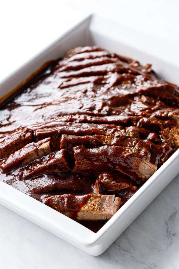 Modern white baking dish with sliced beef brisket and sauce poured over top