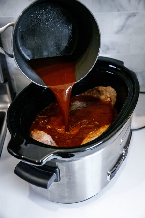 Pouring sauce over brisket in a slow cooker
