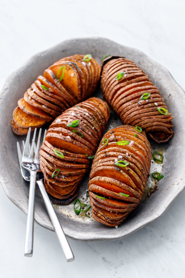 Four Spiced Hasselback Sweet Potatoes arranged on a vintage metal serving plate with two forks, on a white marble background.