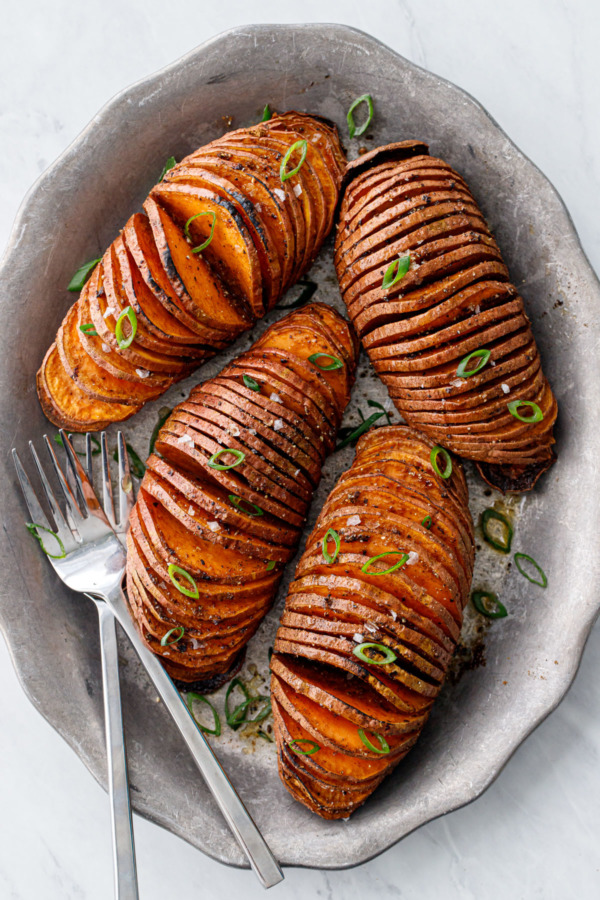 Overhead view of four Hasselback Sweet Potatoes arranged on a metal plate with forks