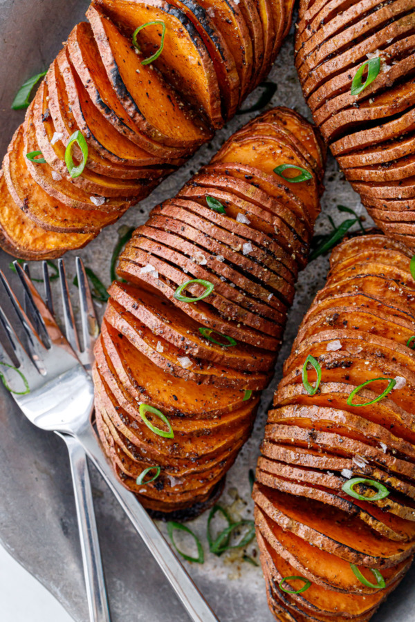 Closeup overhead of four Spiced Hasselback Sweet Potatoes on a metal plate with forks, topped with green onions.