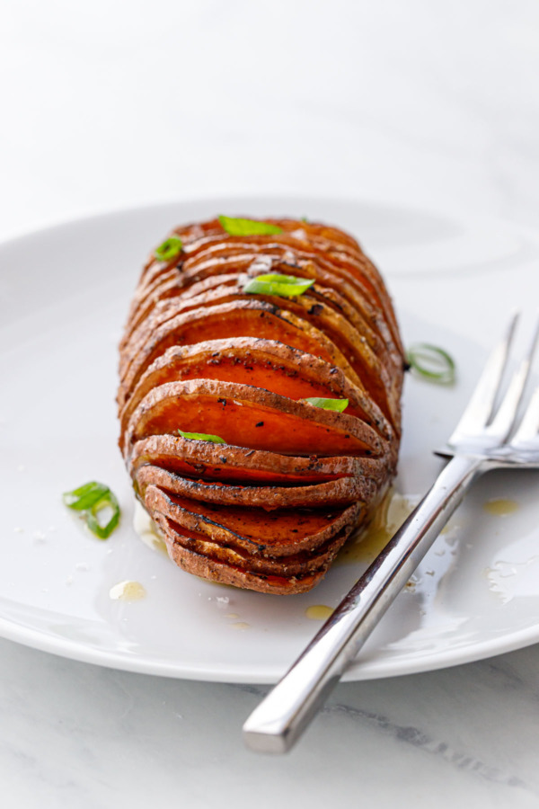 Spiced Hasselback Sweet Potato on a white plate with a fork