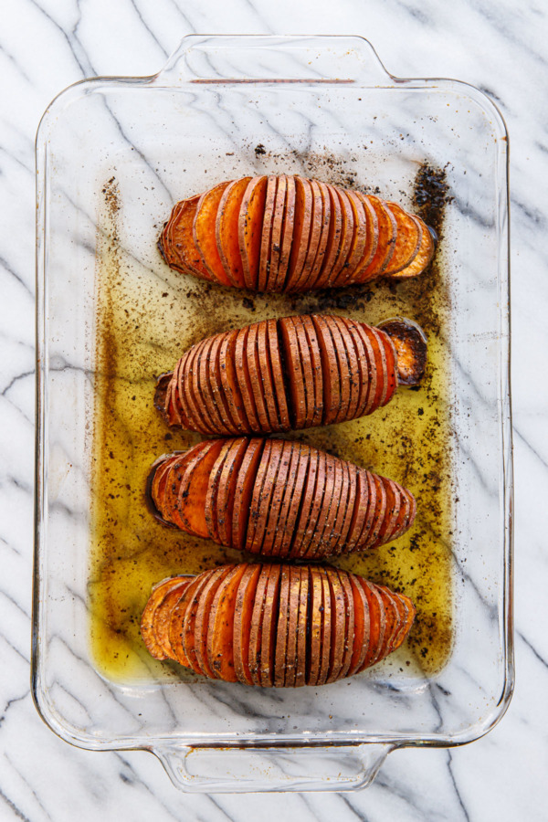 Spiced Hasselback Sweet Potatoes in a glass casserole dish, after baking