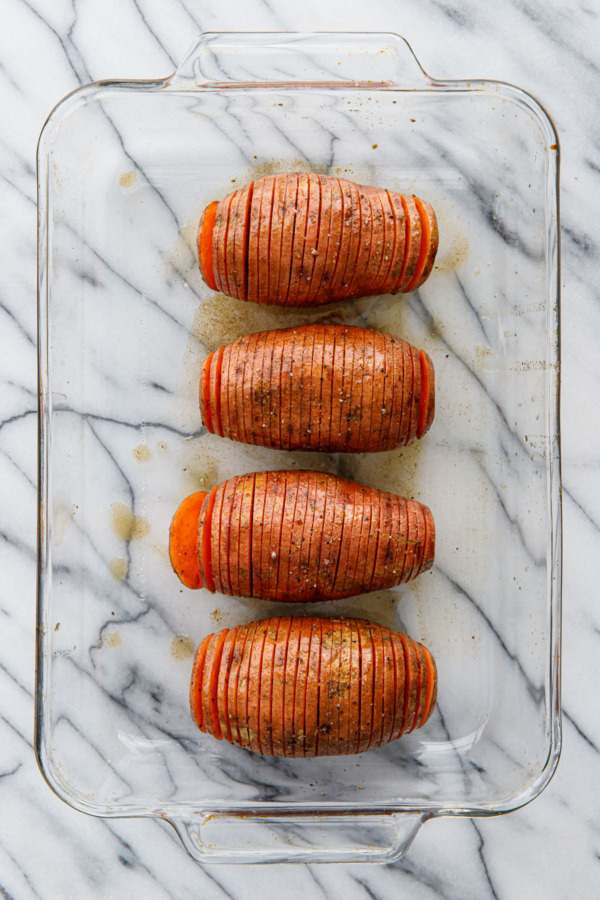 Spiced Hasselback Sweet Potatoes in a glass casserole dish, before baking
