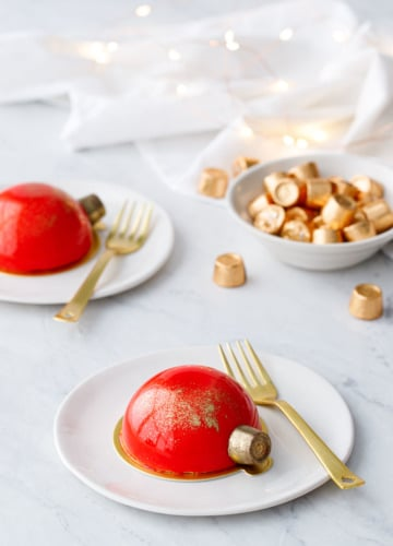 Two red mirror-glazed cakes decorated to look like Christmas ornaments, on white plates with gold forks and fairy lights in the background.
