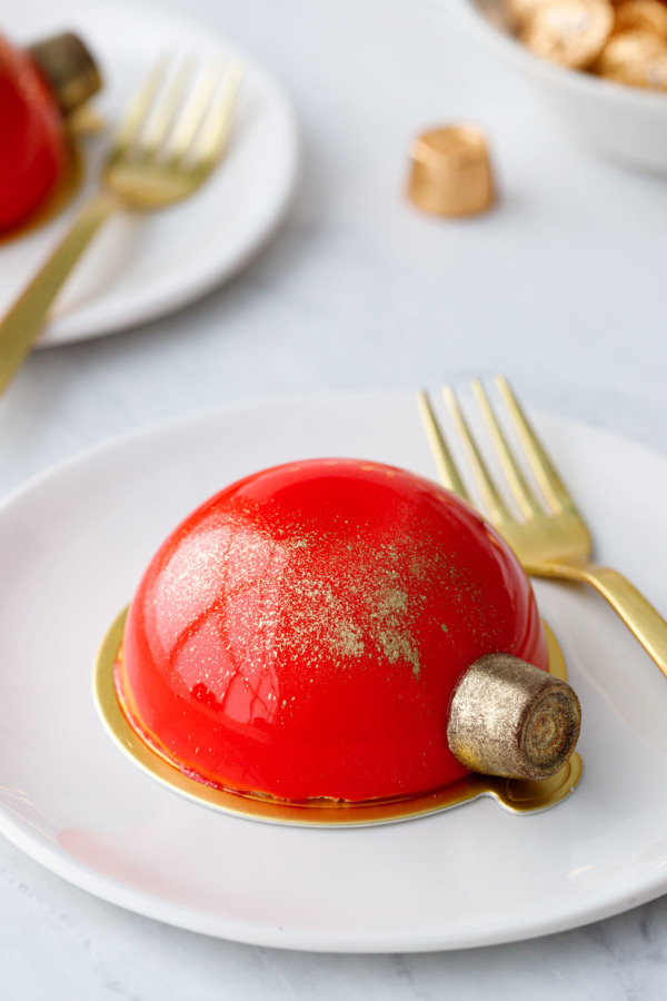 A red mirror-glazed half dome cake with a gold dusted Rolo on the side to look like a Christmas ornament