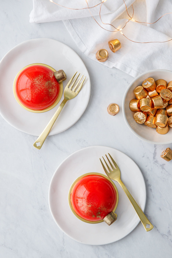 Overhead view of red mirror-glazed entremet cakes decorated to look like Christmas ornaments, with gold forks and a bowl of Rolo candies on the side