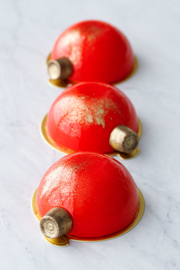 Three red mirror-glazed entremet cakes decorated with gold-dusted Rolo candies to look like Christmas ornaments