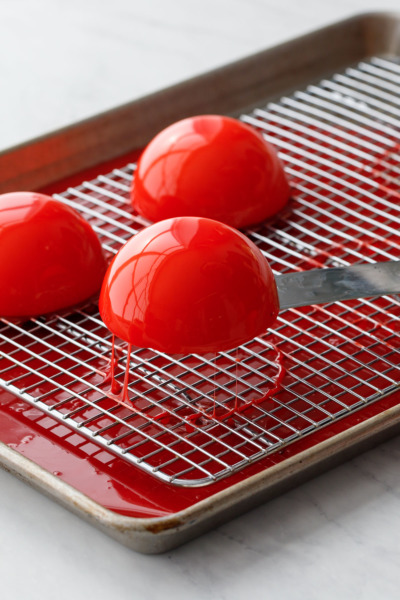 How-To Entremet Cake Process: Use a wet offset spatula to lift the cake off of the wire rack and clean up any drips.