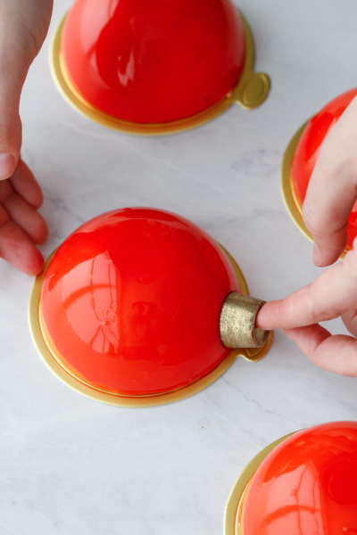 How-To Entremet Cake Process: place a gold-dusted Rolo candy on one side of the cake.