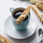 White chocolate dipped biscotti cookie sitting on the rim of a blue gingham coffee cup, with more biscotti in the background.