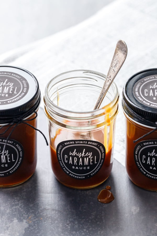 Three backlit jars of whiskey caramel sauce, with a spoon in one partially-empty jar and drips of caramel on the rim.
