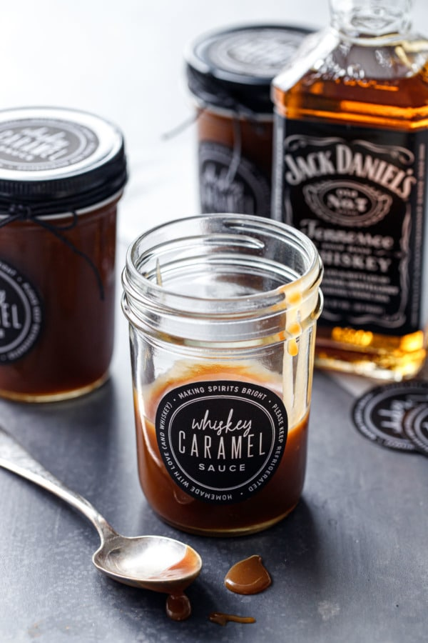 A partially full glass jar of whiskey caramel sauce, with a few more jars and a bottle of Whiskey in the background.