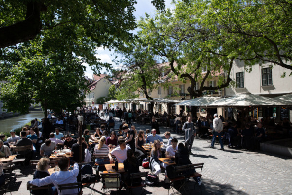 Busy promenade in Ljubljana, Slovenia, filled with people eating at cafes on a sunny day.