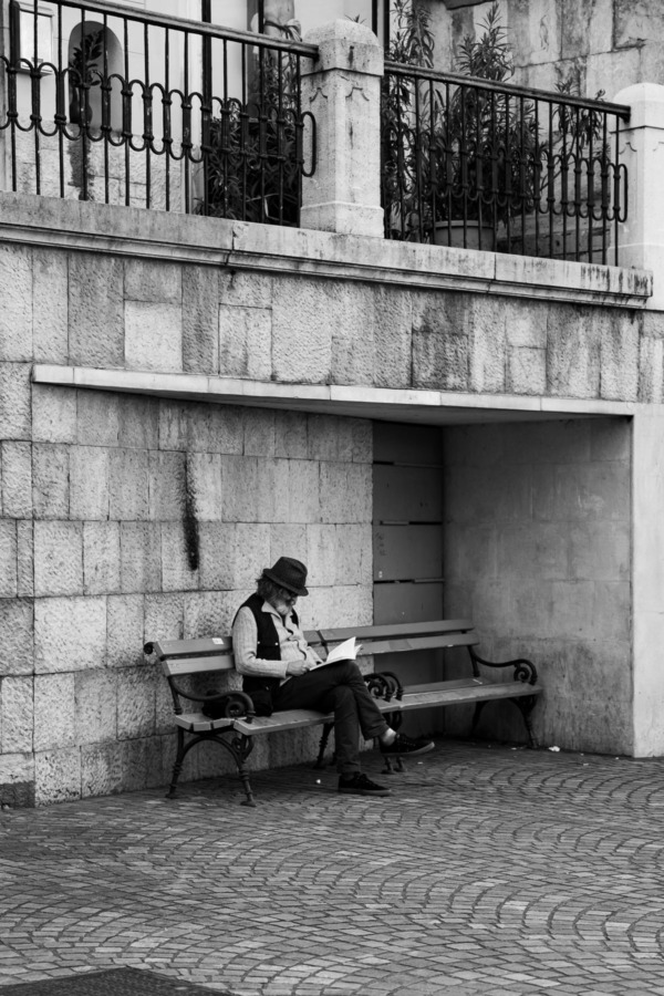 Black and white photo of an old man reading on a bench in Ljubljana, Slovenia