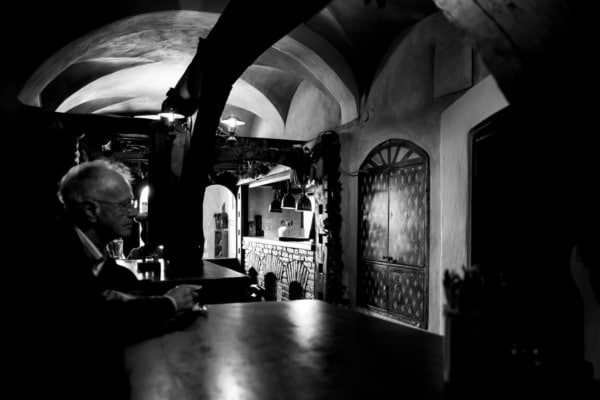Black and white, old man sitting at the table inside an historic restaurant in Ljubljana, Slovenia