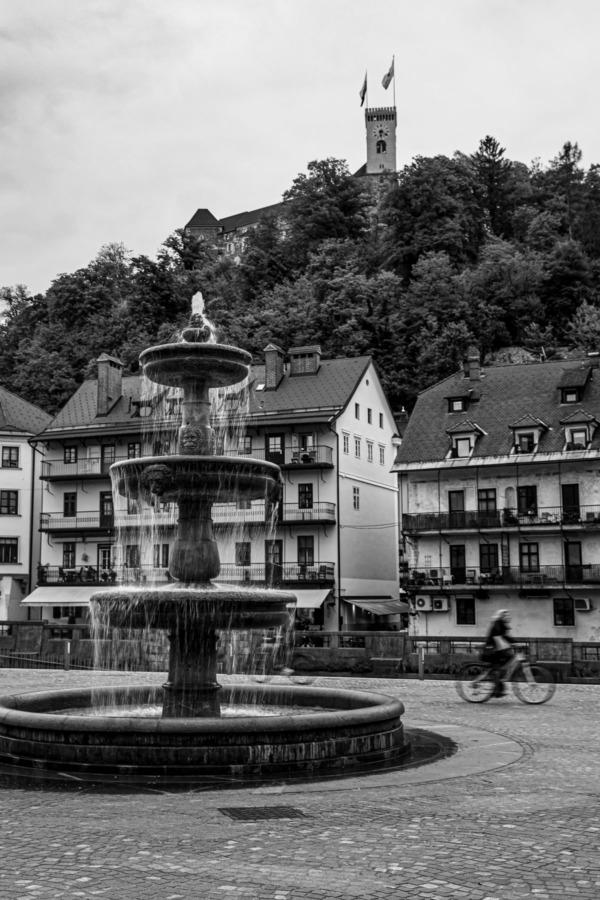 Black and white Novi Trg square and fountain looking towards the castle in Ljubljana, Slovenia