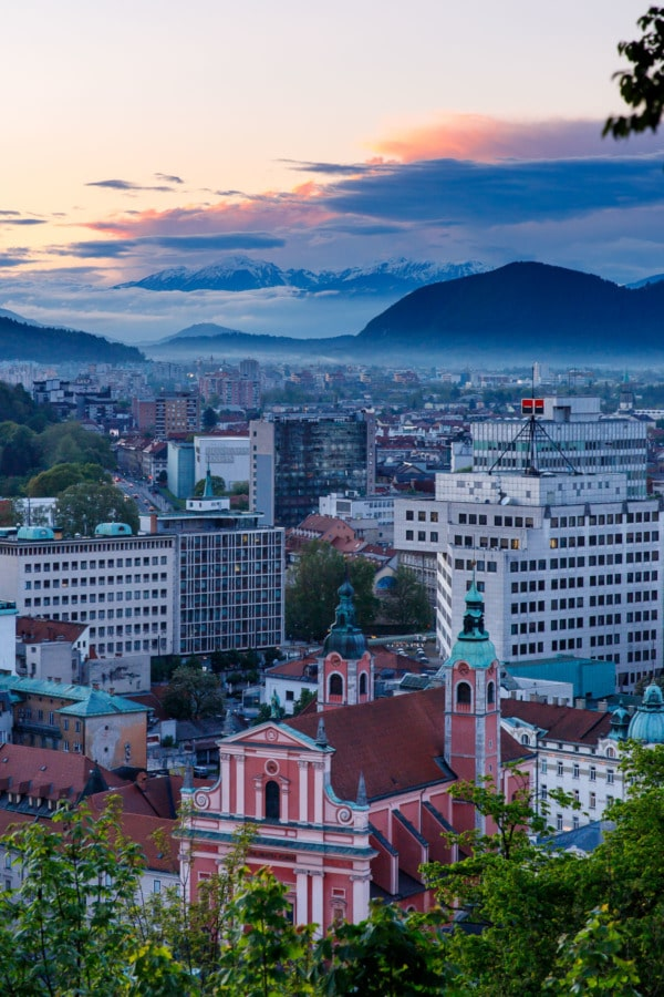 Sunset in Ljubljana, Slovenia, looking out over the city and the snow-covered mountains in the background.