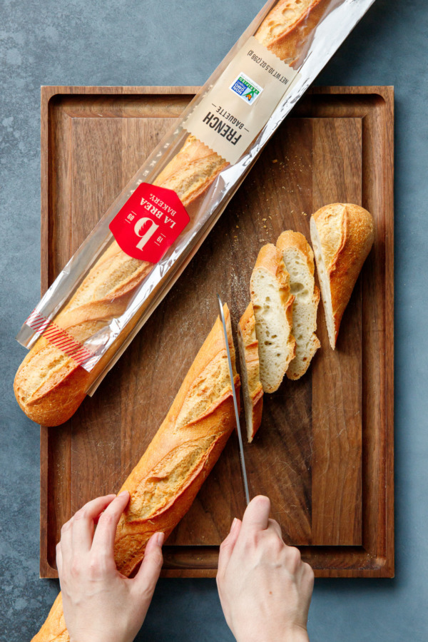 Cutitng a baguette diagonally on a wooden cutting board.