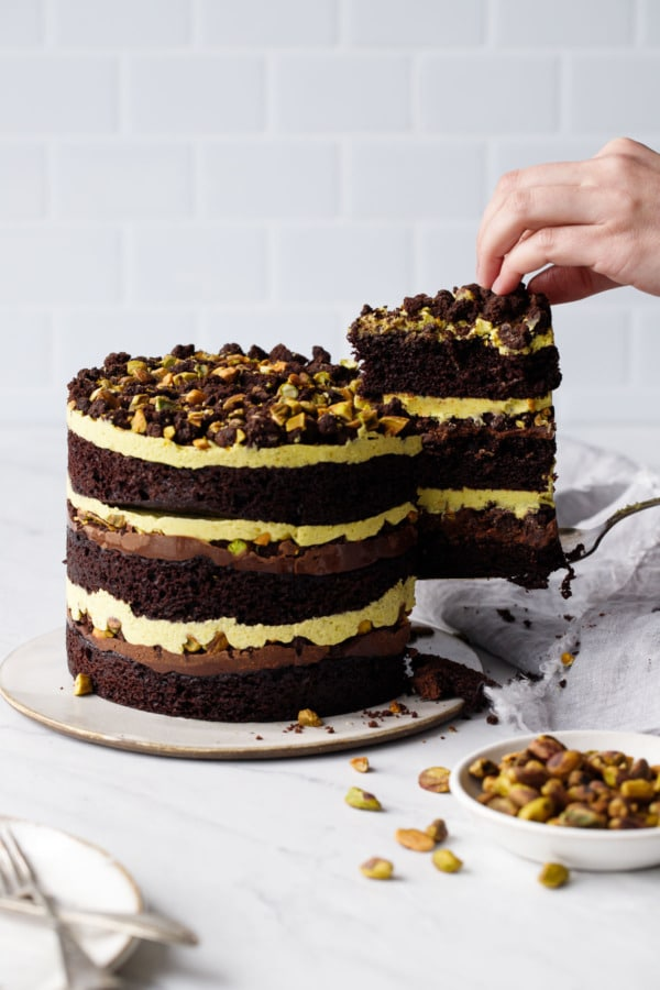Cutting a slice out of the Dark Chocolate Pistachio Naked Layer Cake