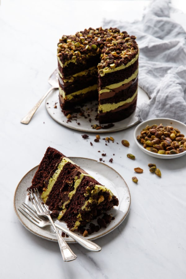 Slice of Dark Chocolate Pistachio Naked Layer Cake with the full cake in the background and a bowl of pistachios.