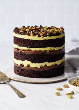 Dark Chocolate Pistachio Naked Layer Cake on a white background with a bowl of pistachios and cake server.