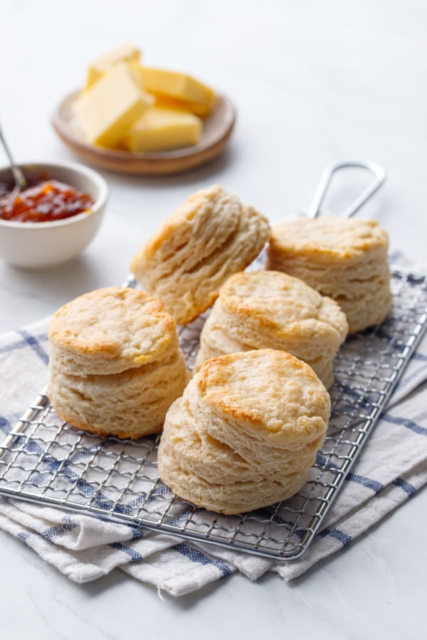 Tall, flaky sourdough biscuits on a cooling rack with butter and marmalade