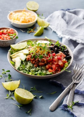 Turkey Taco Bowls with Cilantro Rice on a dark blue background with bowls of salsa and cheese and slices of lime scattered around.