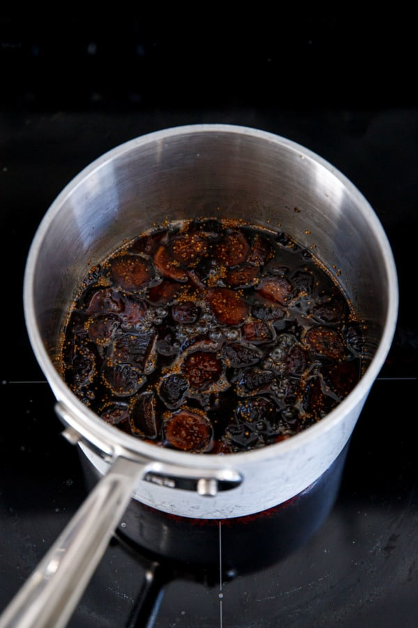 Simmering dried figs in syrup to make homemade fig syrup