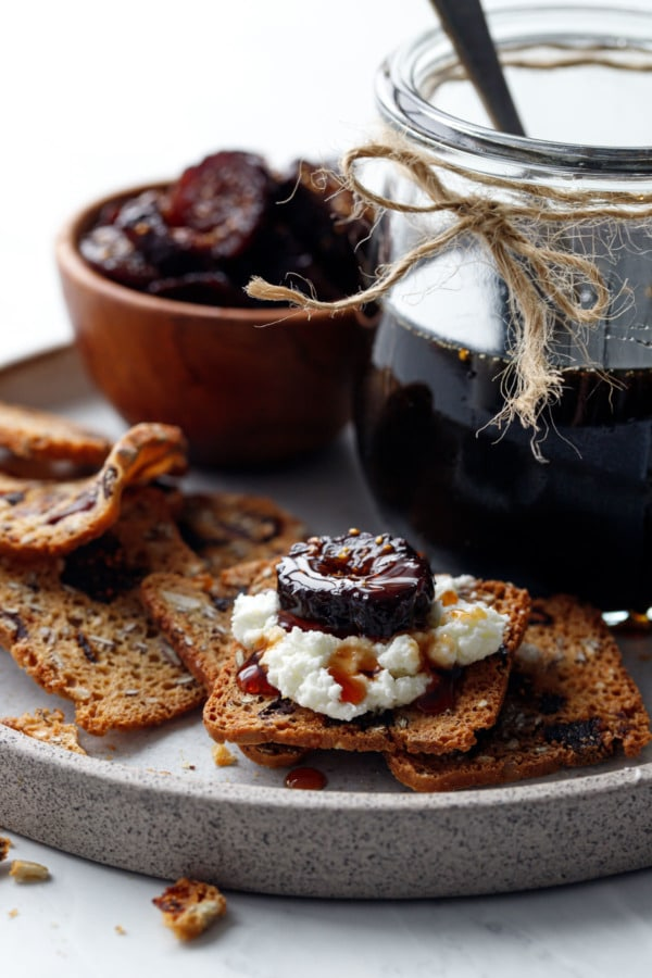 Homemade Fig Syrup, served on crackers spread with goat cheese and topped with a slice of dried fig