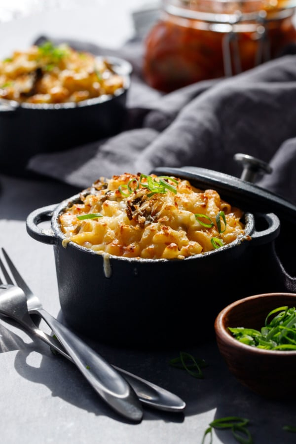 Creamy white cheddar Macaroni & Cheese with Kimchi in black ramekins with sliced scallion