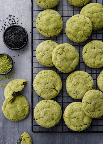Overhead shot with a cooling rack with rows of matcha sugar cookies, bowls of matcha powder and black sesame seeds.