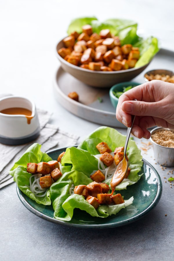 Spooning spicy peanut sauce onto Baked Tofu Lettuce Wraps