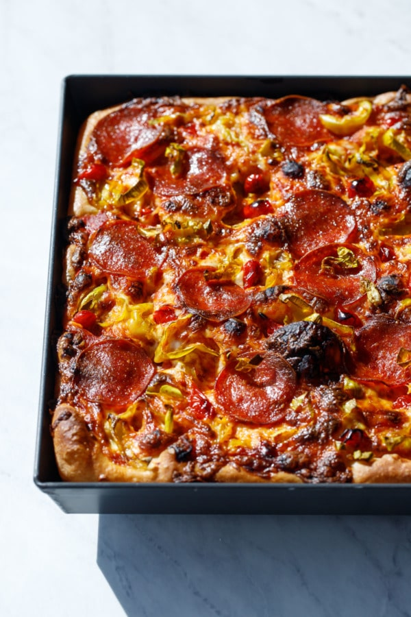 Detroit-style pan pizza styled in harsh light topped with pepperoni and pickled peppers.