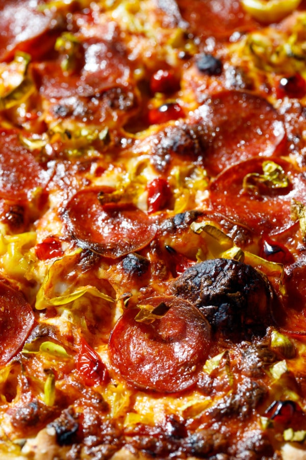 Closeup of toppings and blackened bubbles on a pan pizza.