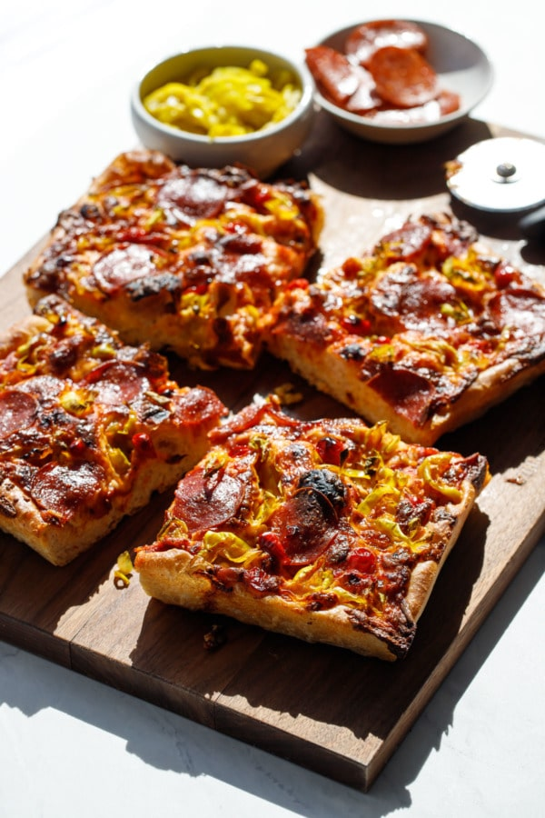Sliced Detroit-Style Pepperoni and Pickled Pepper Pan Pizza, shot in harsh light on a wooden cutting board