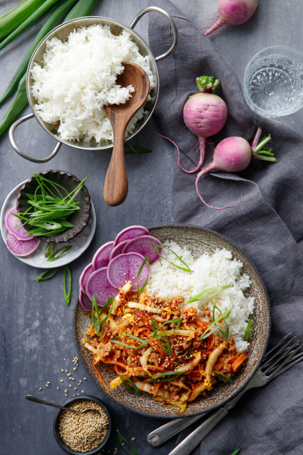 Overhead shot of bowl of Spicy Korean Egg Roll Bowls with a dish of white rice and purple radishes.