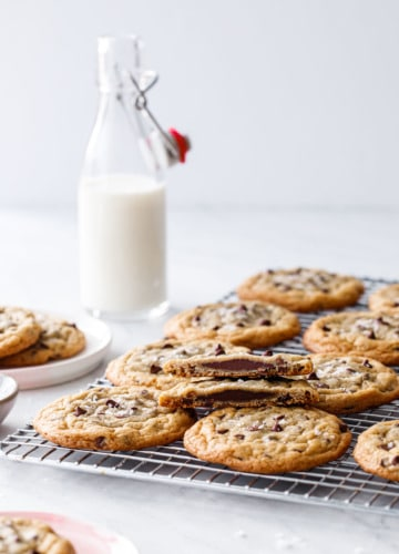 Ganache-Stuffed Chocolate Chip Cookies on a wire rack with a glass milk bottle