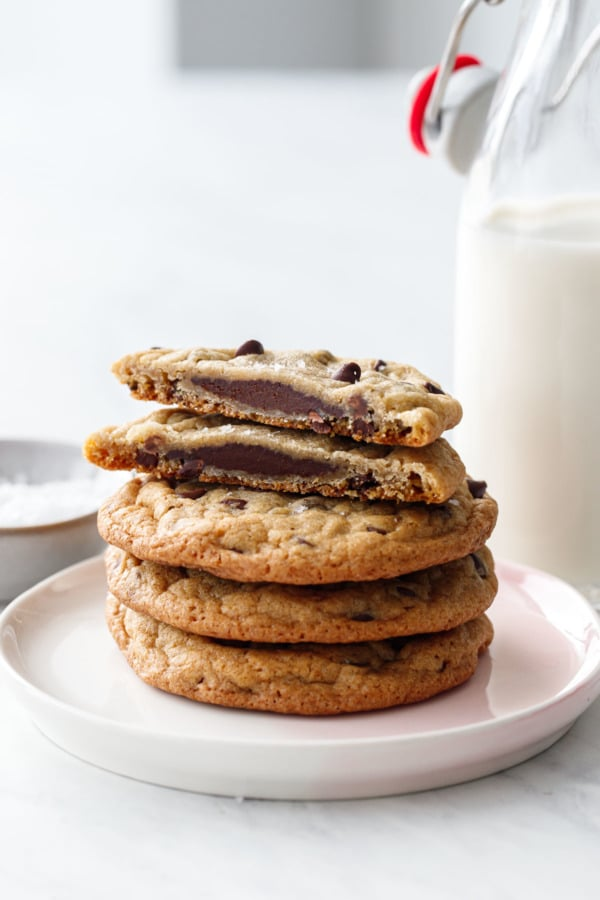 Stack of cookies, one cut in half to show the ganache filling, with a milk bottle in the background.