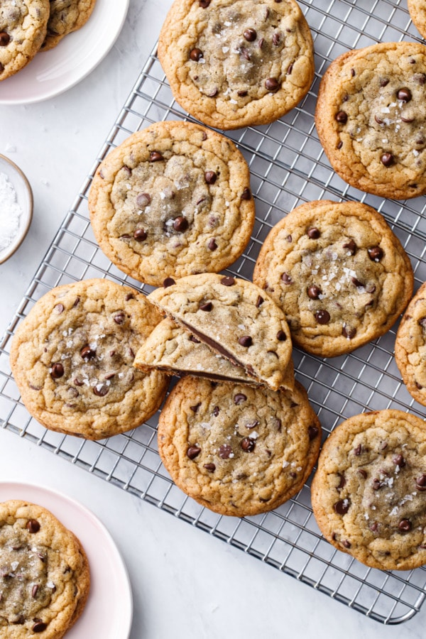 Overhead of Ganache-Stuffed Chocolate Chip Cookies on a wire rack with a small bowl of flake sea salt