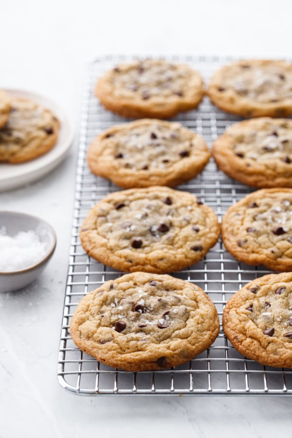 Ganache-Stuffed Chocolate Chip Cookies on a wire cooking rack with a small bowl of flake sea salt