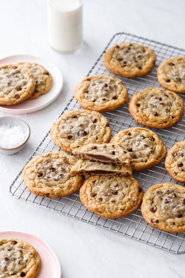 Ganache-Stuffed Chocolate Chip Cookies on a wire rack with a bowl of flake salt and milk bottle.