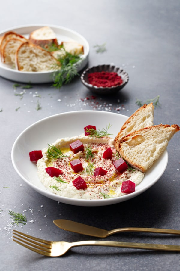 White bowl with whipped almond dip, topped with pickled beets and two slices of fresh sourdough.