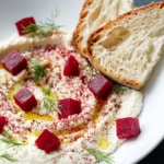 Closeup of white bowl with Whipped Almond Dip, topped with Pickled Beets, fresh dill and two slices of Sourdough